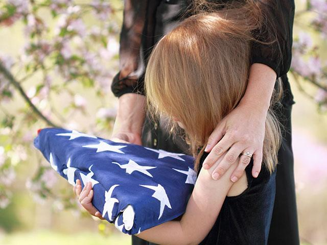 Daughter holding a folded American flag