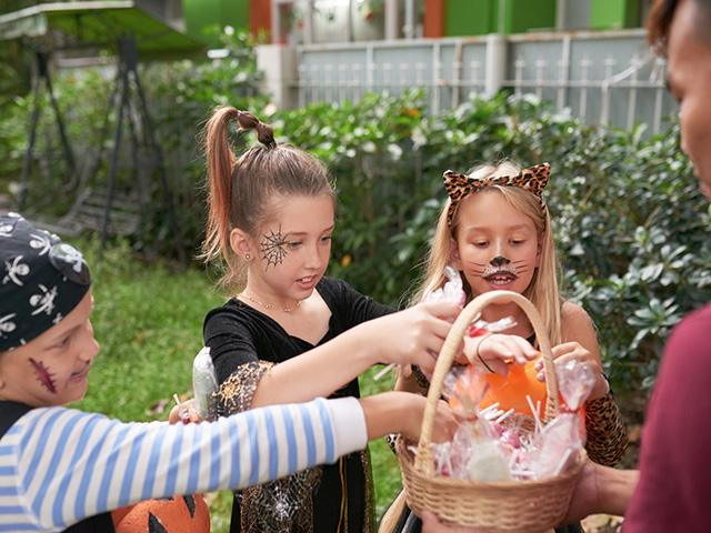 children on halloween getting trick or treat candy from person in a house