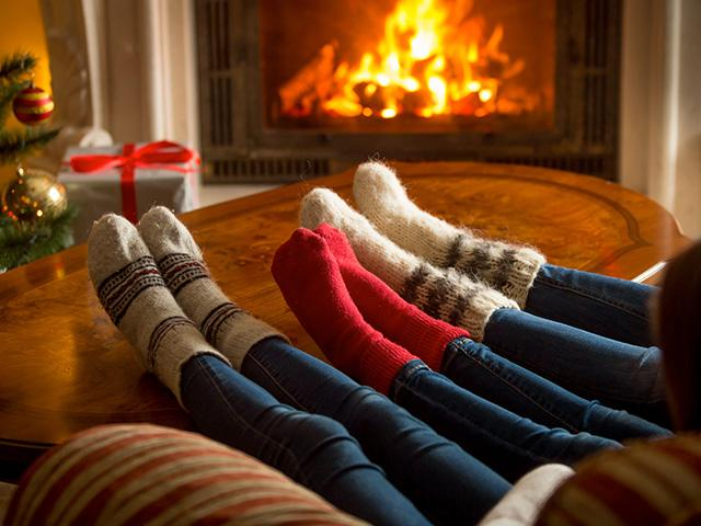 sock-feet propped on coffee table near the fireplace