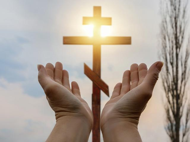 hands opening to a cross in the sunny sky