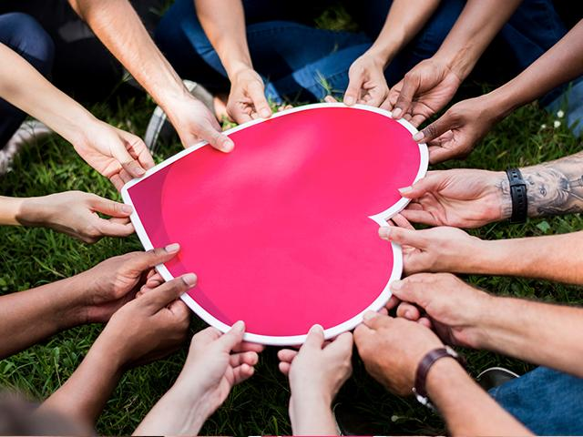 group of people holding a big heart