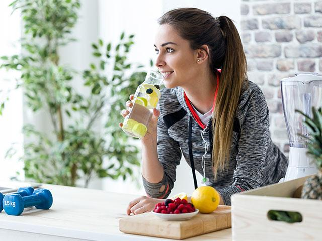 healthy young woman drinking water with lemon
