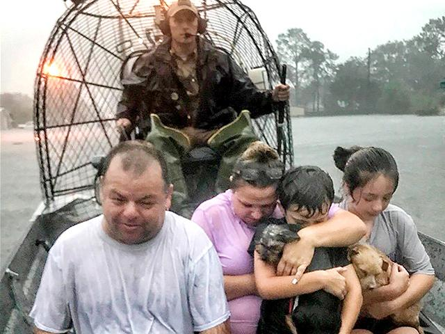 A family is rescued via fan boat by from the flood waters of Tropical Depression Imelda near Beaumont, Texas, Sept. 19, 2019. (Texas Parks & Wildlife Department via AP)