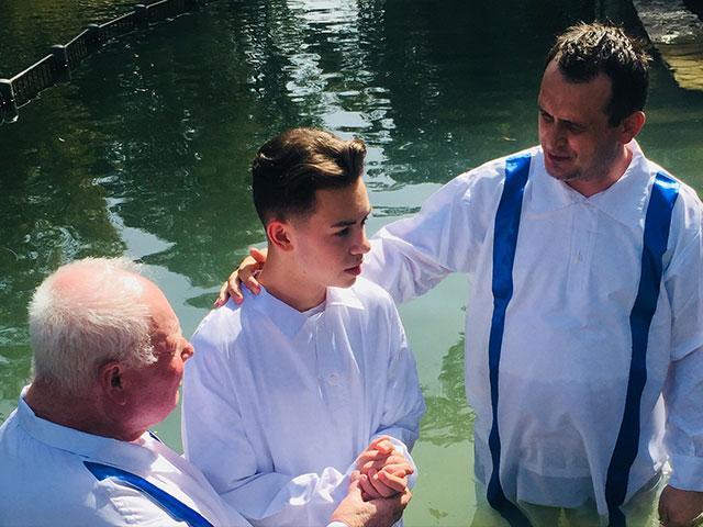 Bishop Doru de Ilioi, right, prepares to baptize Eldad, a young man who asked to be baptized after watching Mario Lopez's baptism. On the left is Petre Ursu who assisted. Photo courtesy: Bishop Doru de Ilioi.