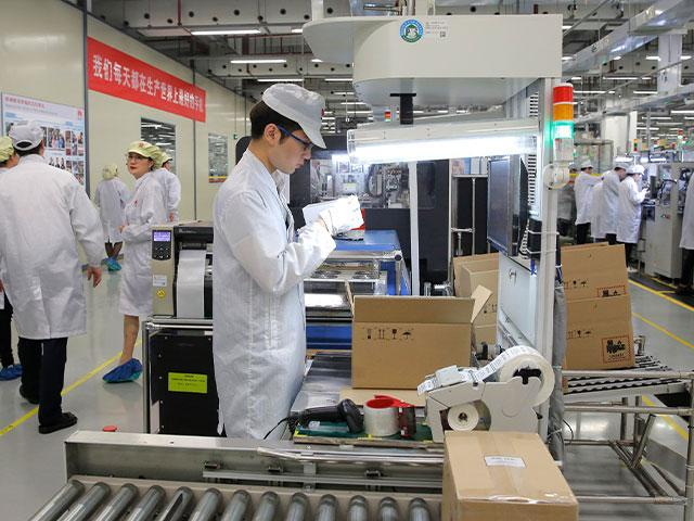 In this March 6, 2019, file photo a staff member works on a mobile phone production line during a media tour in Huawei factory in Dongguan, China's Guangdong province. (AP Photo/Kin Cheung, File)