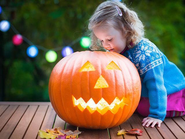 Girl with pumpkin at Halloween