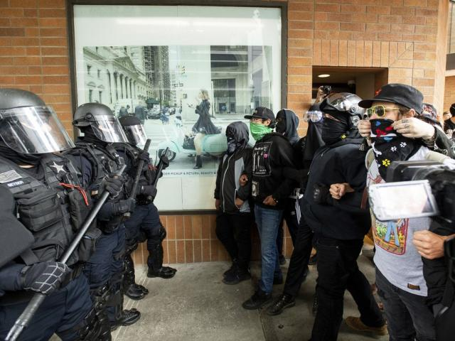 "Police officers face off against protesters following an ""End Domestic Terrorism"" rally in Portland, Ore., on Saturday, Aug. 17, 2019 (AP Photo/Noah Berger)"