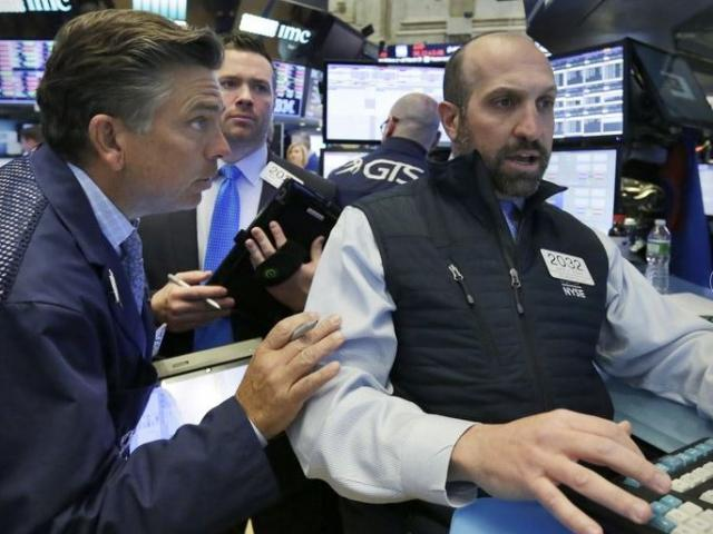 Specialist James Denario, right, works with traders on the floor of the New York Stock Exchange.