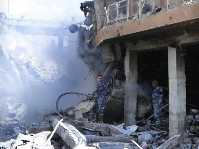 Firefighters stand in smoke that rises from the damage of the Syrian Scientific Research Center which was attacked by U.S., British and French military strikes to punish President Bashar Assad for suspected chemical attack against civilians.