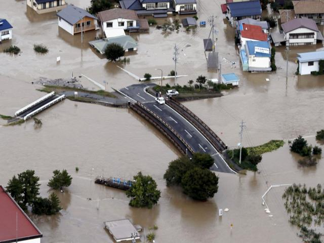 Cars are stranded on a road as the city is submerged in muddy waters after an embankment of the Chikuma River broke, in Nagano, central Japan, Sunday, Oct. 13, 2019 (Yohei Kanasashi/Kyodo News via AP)