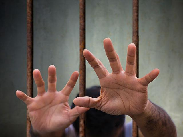 hands reaching out from prison bars