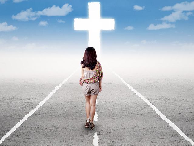 woman walking on the road toward the cross