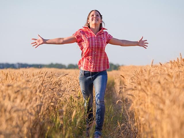 woman running in a wheat field