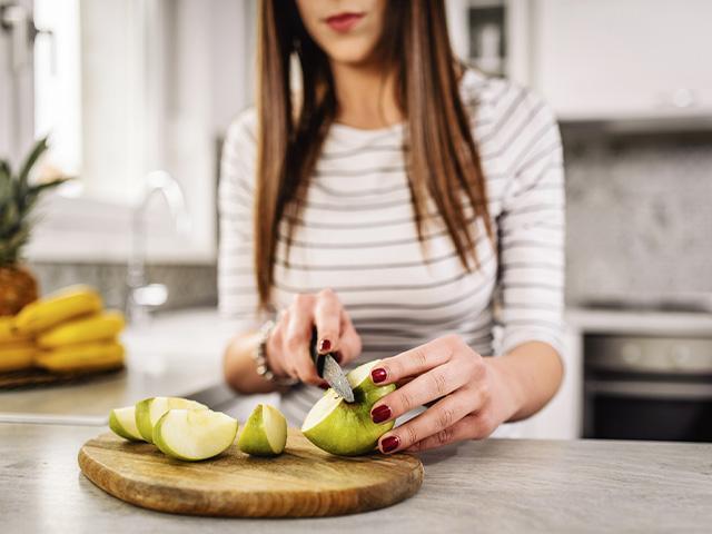 woman cutting apple slices on a cutting board