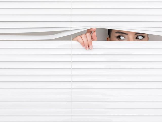woman peeking out from her window blinds