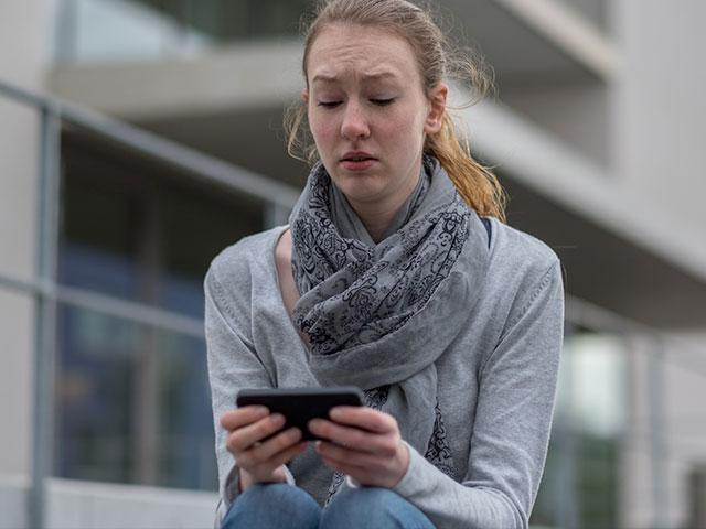Young woman staring at smartphone