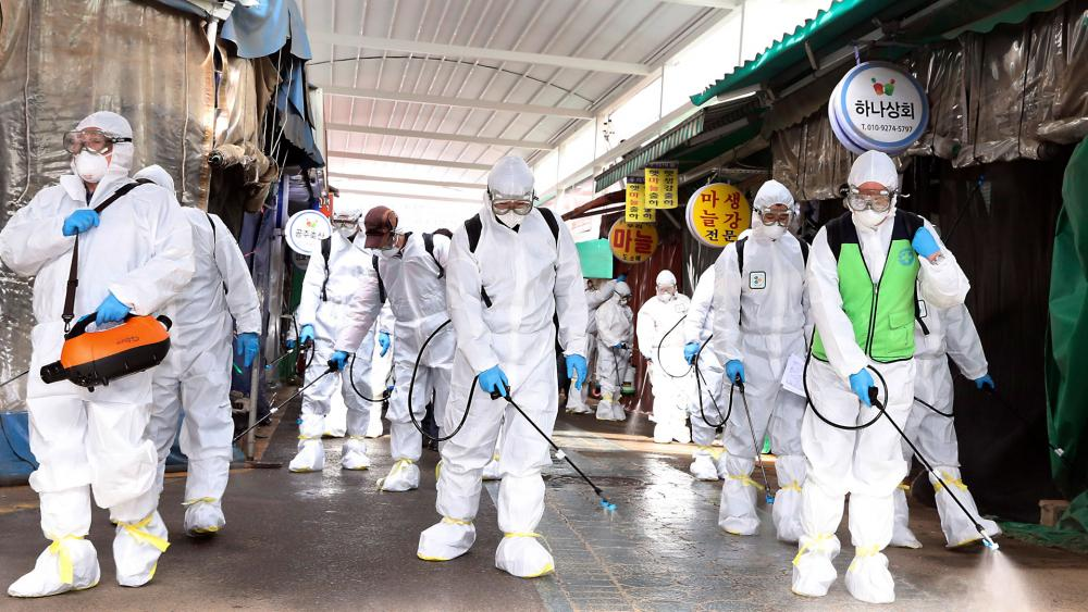 Workers wearing protective suits spray disinfectant as a precaution against the coronavirus at a market in Bupyeong, South Korea, Feb. 24, 2020. South Korea reported another large jump in new virus cases. (Lee Jong-chul/Newsis via AP)