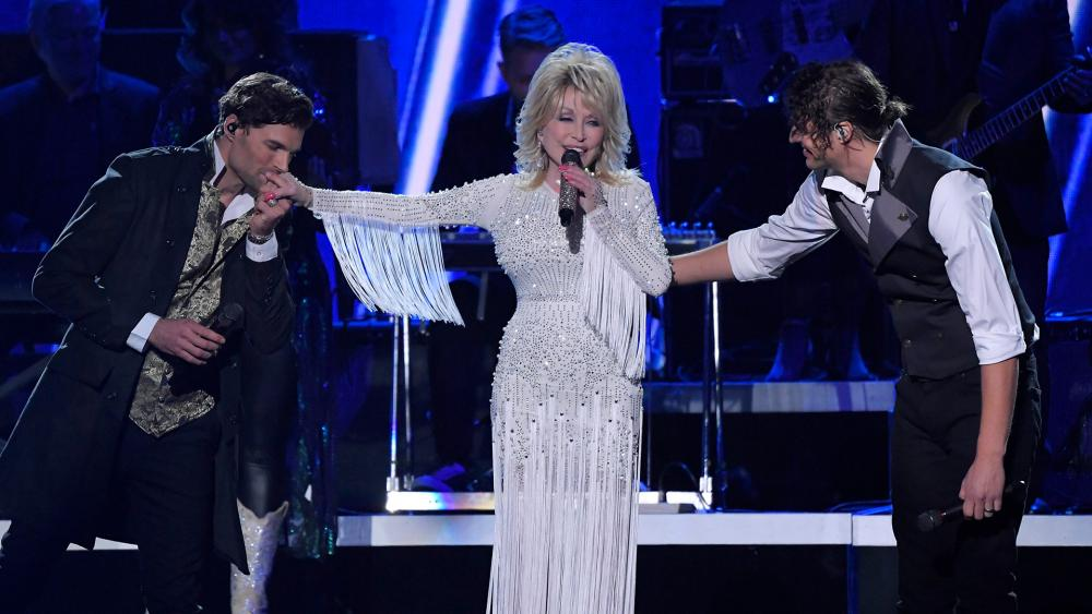 "Dolly Parton performs ""God Only Knows"" with Joel Smallbone, left, and Luke Smallbone, right, of For King & Country at the 53rd annual CMA Awards, Nov. 13, 2019. (AP Photo/Mark J. Terrill)"