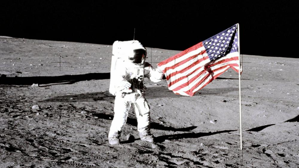 "Charles ""Pete"" Conrad Jr., the third human to walk on the moon on the Apollo 12 mission, stands with the U.S. flag on the lunar surface. (Image courtesy: NASA)"