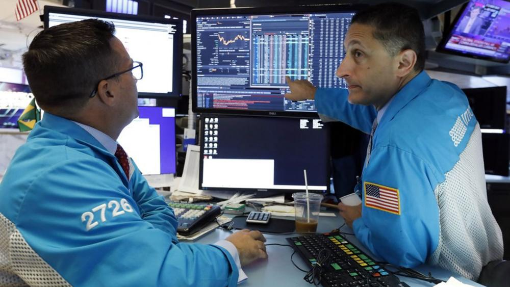 Specialists Paul Cosentino, left, and Jeffrey Berger work on the floor of the New York Stock Exchange, Monday, Aug. 5, 2019.  (AP Photo/Richard Drew)